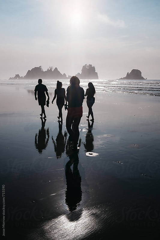 group of friends walking on beach during vacation getaway by Jesse Morrow for Stocksy United