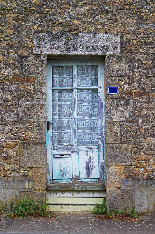 An old faded blue doorway in an old house in France by Sara Wager for Stocksy United