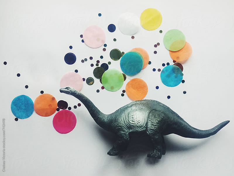 A toy dinosaur and confetti by Chelsea Victoria for Stocksy United