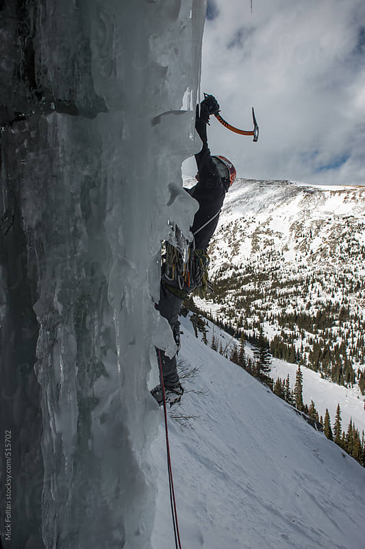 Ice climber swings into steep ice. by Mick Follari for Stocksy United