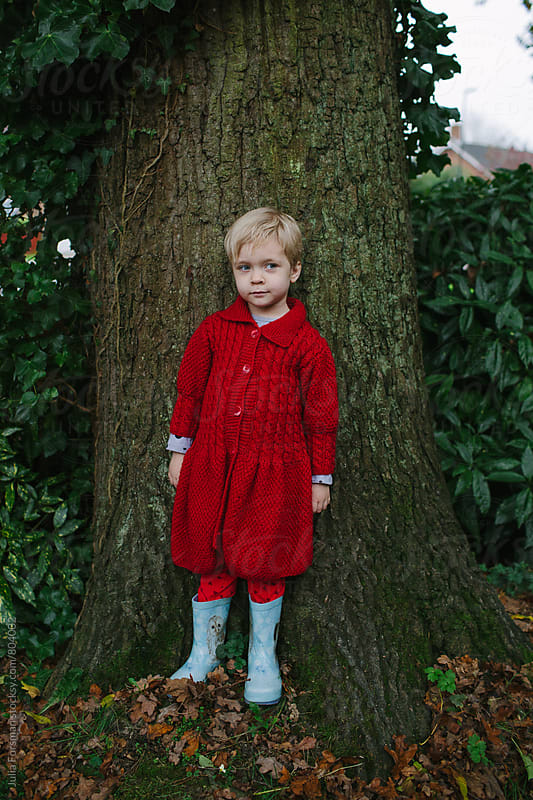 Girl in red cardigan standing against a tree by Julia Forsman for Stocksy United