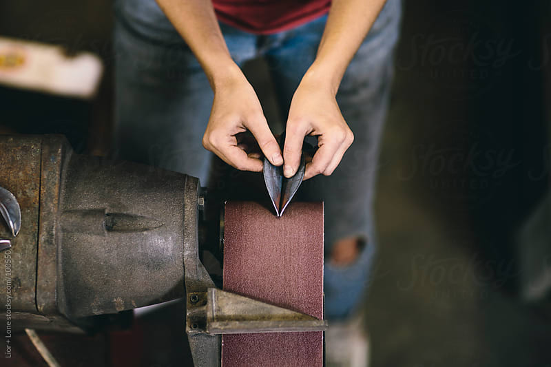 Closeup of woman's hands  sanding metal on belt sander by Lior + Lone for Stocksy United