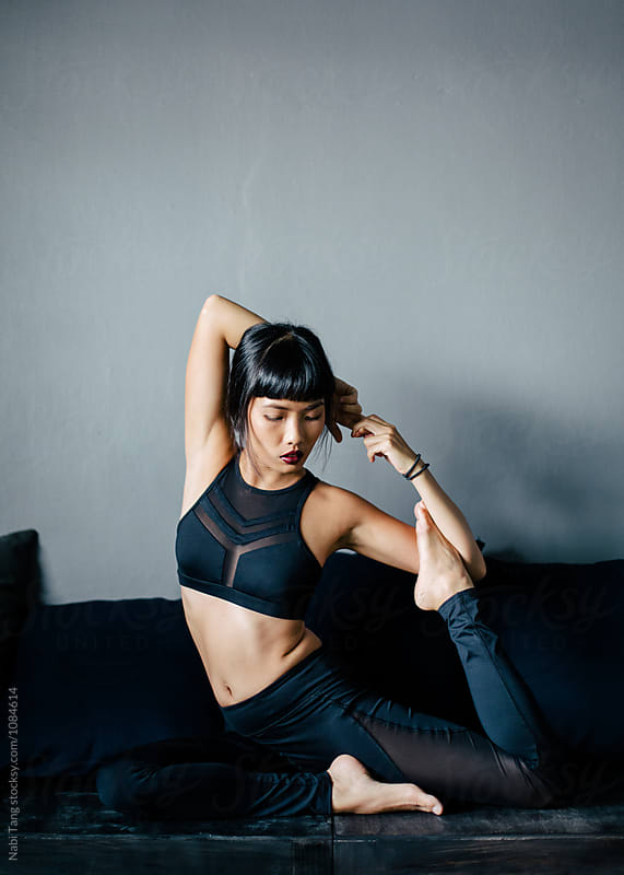 Asian woman doing yoga by Nabi Tang for Stocksy United