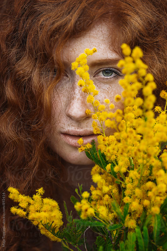Portrait of a beautiful redhead with yellow flowers in the foreground by Maja Topcagic for Stocksy United