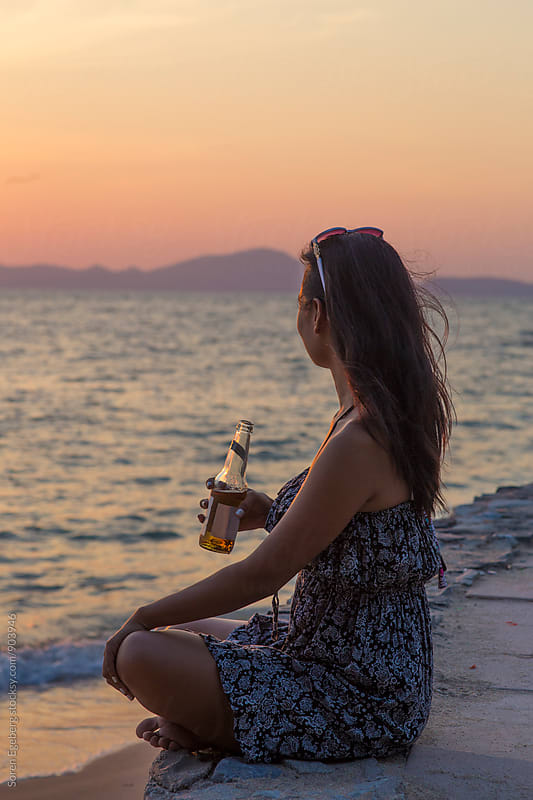Woman drinking a beer at sunset  by Søren Egeberg Photography for Stocksy United