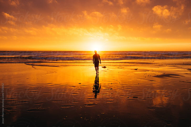 young male silhouette walking away from water at sunset with reflection  by Jesse Morrow for Stocksy United