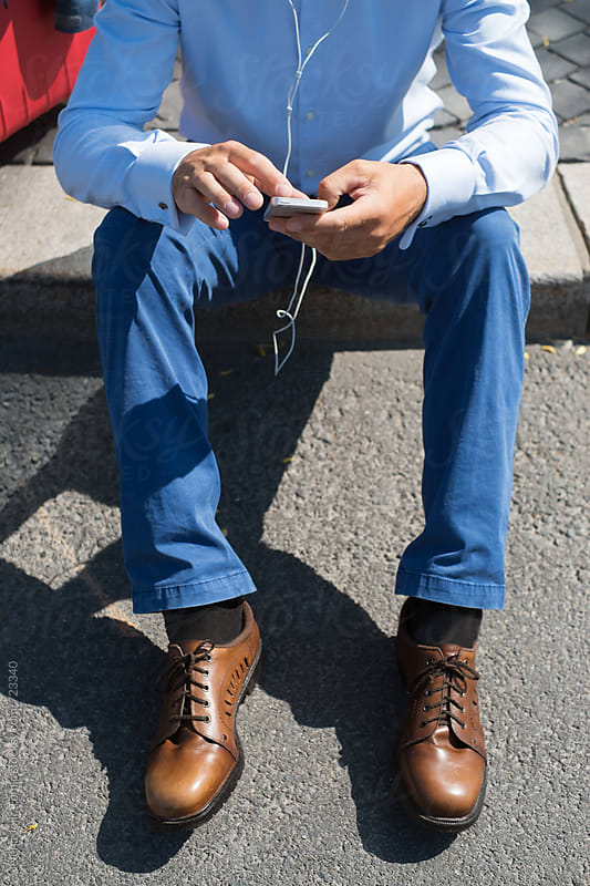 Businessman is sitting on a sidewalk, checking on his phone by Jelena Jojic Tomic for Stocksy United