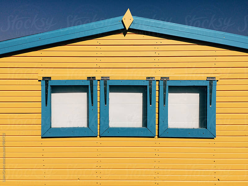 Yellow wooden panelled beach hut with blue windows. Norfolk, UK. by Liam Grant for Stocksy United