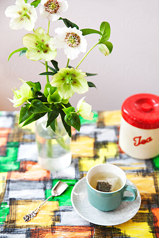 Table with vintage tablecloth and cup of tea by Natalie JEFFCOTT for Stocksy United