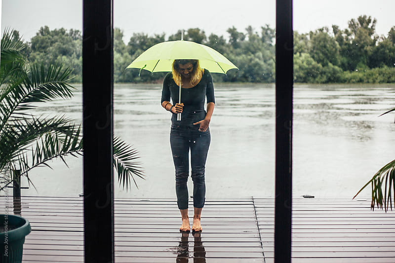 Barefoot woman by the river on a rainy day by Jovo Jovanovic for Stocksy United