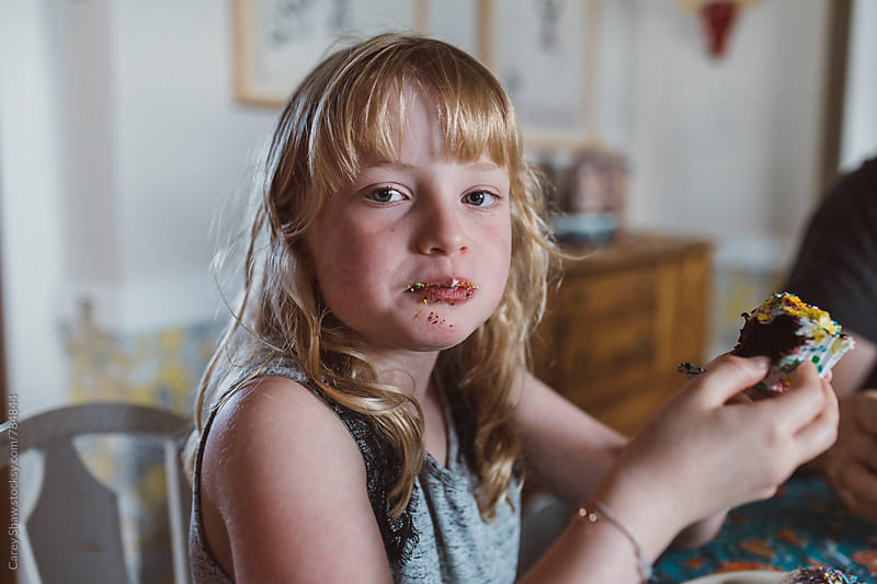 Young girl eating cupcake with messy face by Carey Shaw for Stocksy United