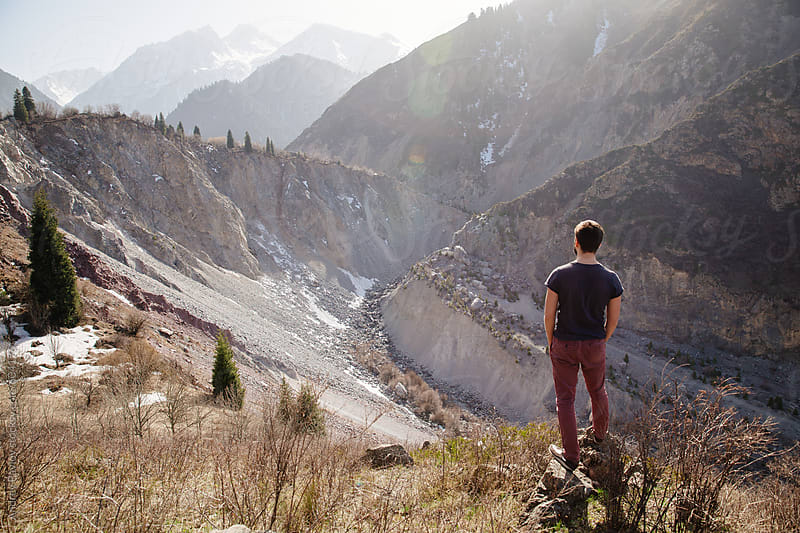 Man looking at mountains by Andrey Pavlov for Stocksy United