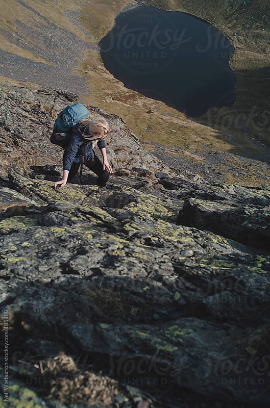 Young Woman Climbing on a Mountain Ridge by Neil Warburton for Stocksy United
