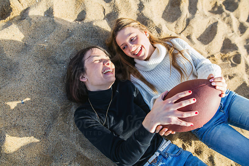 Happy best friends playing with a ball on the beach. by BONNINSTUDIO for Stocksy United