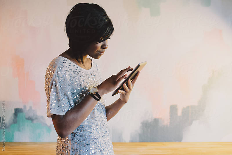 Black girl using a tablet in front of a painted wall by Gabrielle Lutze for Stocksy United