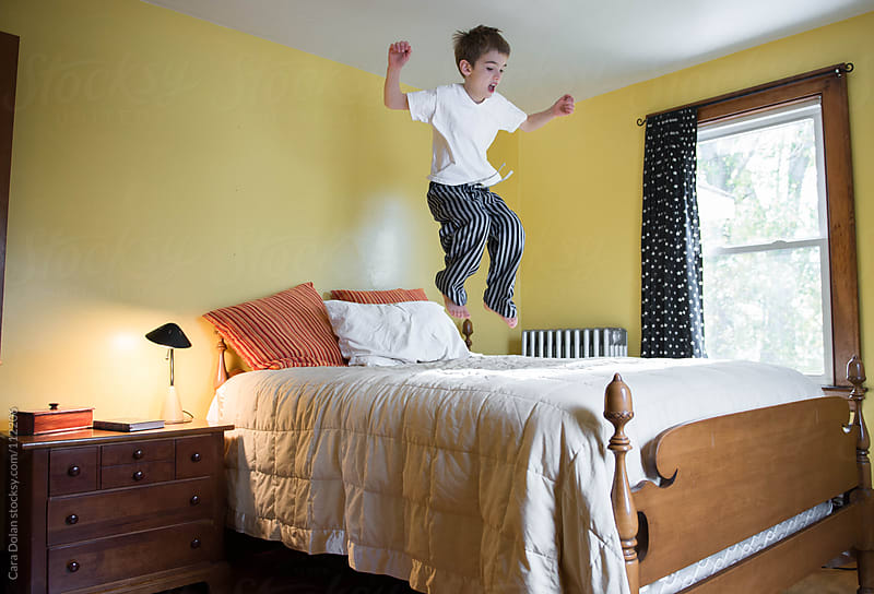 Boy jumps happily on his bed by Cara Dolan for Stocksy United