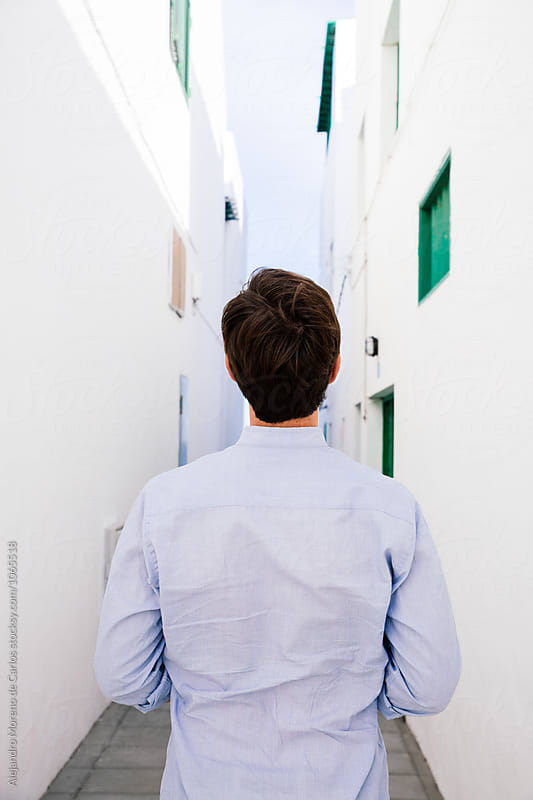 Back view of man standing in narrow street with white walls by Alejandro Moreno de Carlos for Stocksy United