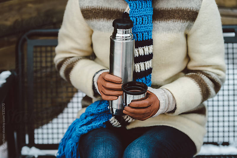 Woman drinking hot chocolate from vacuum flask by Jen Grantham for Stocksy United