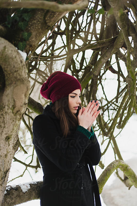 Winter portrait of a beautiful brunette  trying to get her hands warm by Natasa Kukic for Stocksy United