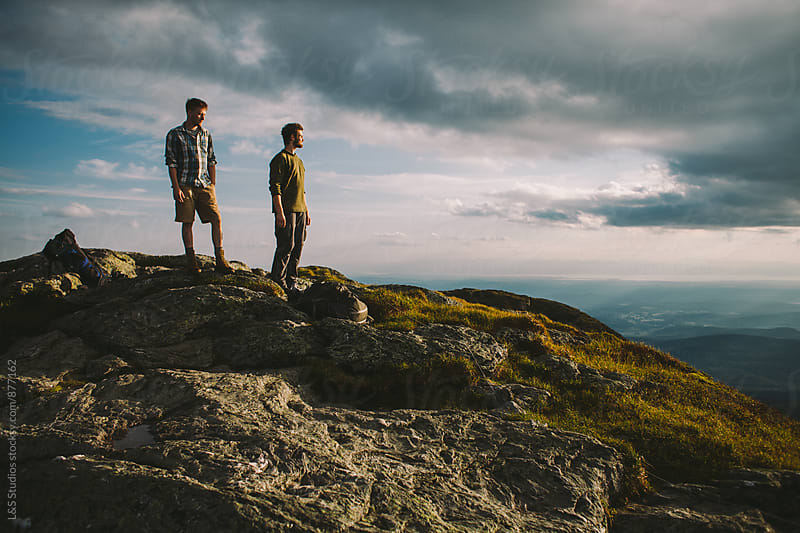 2 men on a mountain peak. by L&S Studios for Stocksy United