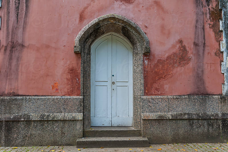 Blue colonial doorway with red rendered walls by Ben Ryan for Stocksy United