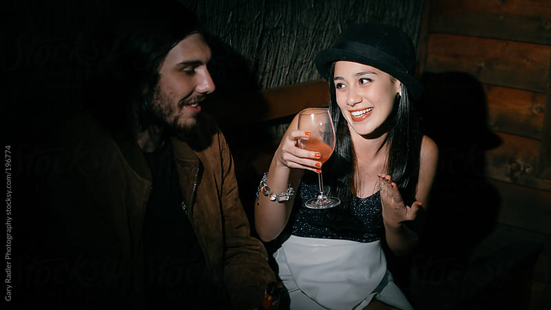 Young man and woman in conversation at a party by Gary Radler Photography for Stocksy United