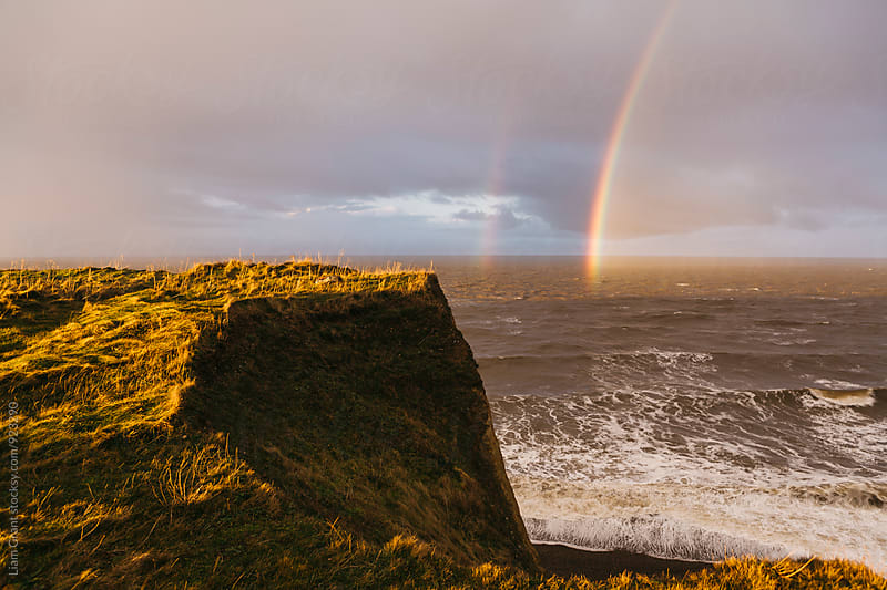 Rainbow and stormy sky at sunset. Sheringham, Norfolk, UK. by Liam Grant for Stocksy United