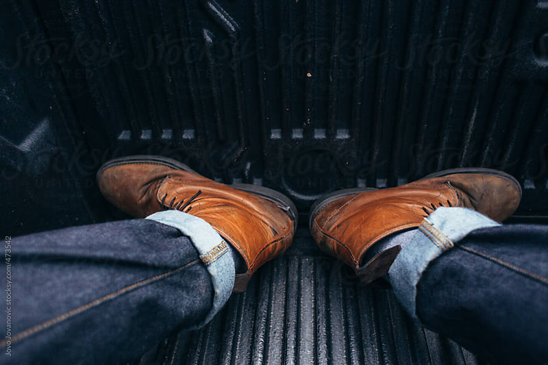 Mans brown country style leather boot and jeans by Jovo Jovanovic for Stocksy United