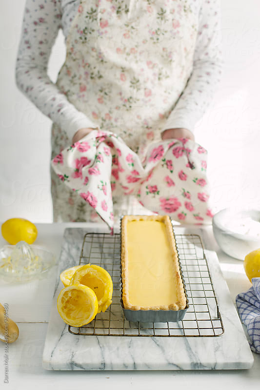 Woman preparing a lemon tart: Woman placing a freshly baked lemon tart on cooling rack. by Darren Muir for Stocksy United