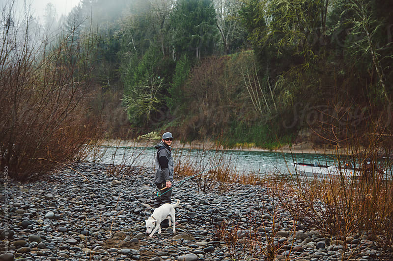 Fly fisherman walking along the rocky shore of a river with his dog by Kate Daigneault for Stocksy United