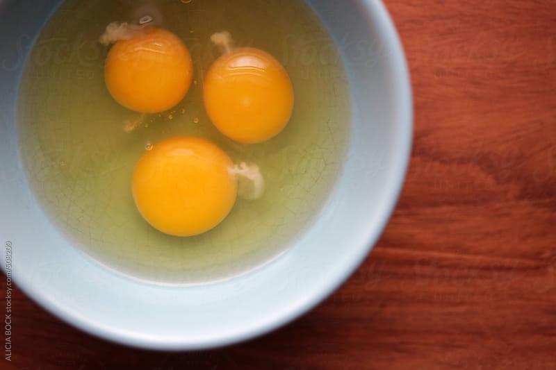 Three Egg Yolks In A Blue Bowl by ALICIA BOCK for Stocksy United