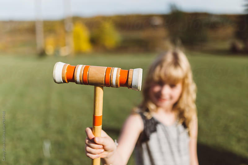 Young girl holding orange croquet mallet by Carey Shaw for Stocksy United