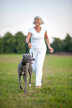 senior woman outdoors with her pet dog by Lee Avison for Stocksy United
