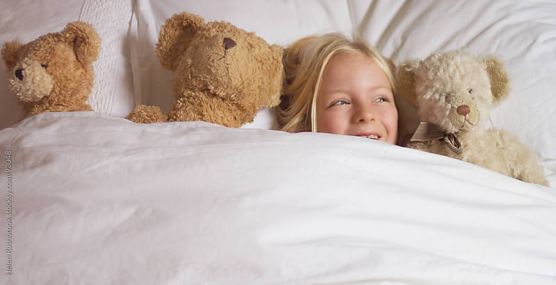 A little girl in bed with her teddy bears. by Helen Rushbrook for Stocksy United
