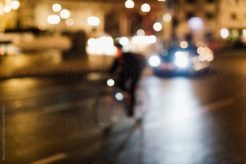 Man riding a Bicycle at night by Mauro Grigollo for Stocksy United