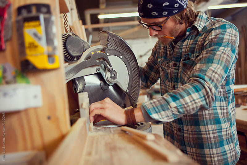 Woodworking: Employee Using Radial Saw To Cut Trim by Sean Locke for Stocksy United