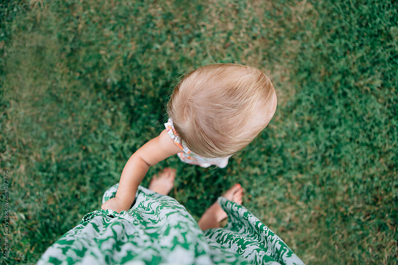 toddler holding her mother's skirt by Meaghan Curry for Stocksy United