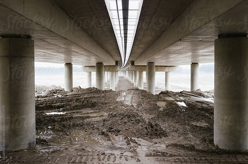 Mud under a highway bridge cross a river by Maa Hoo for Stocksy United