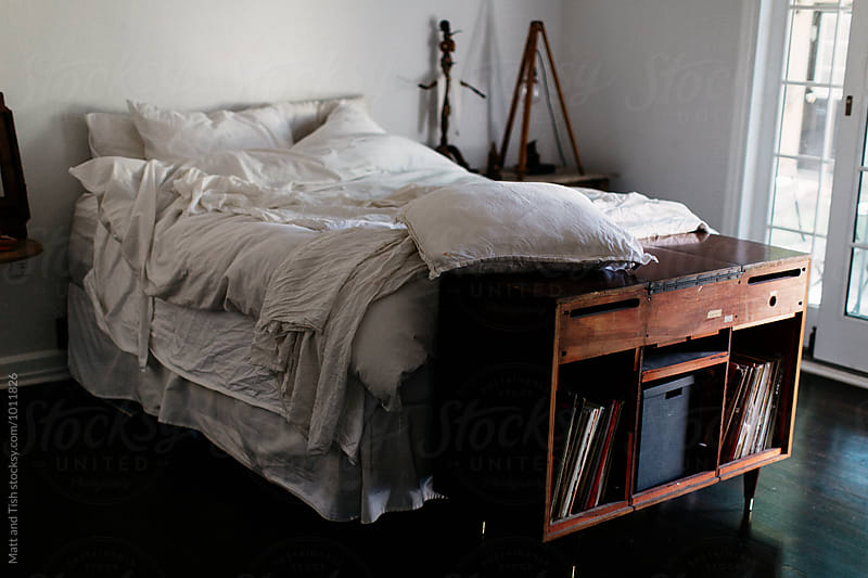 Bedroom with unmade bed by Matt and Tish for Stocksy United