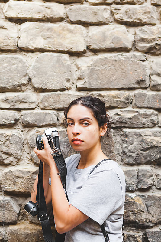 Young Photographer with Analog Camera in front of an Old Stone Wall by Giorgio Magini for Stocksy United