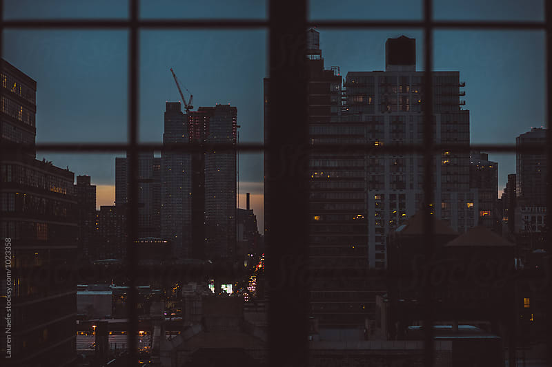City seen through window at dawn by Lauren Naefe for Stocksy United