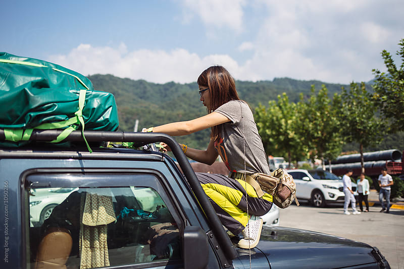 The girl is tying the luggage on the car by zheng long for Stocksy United