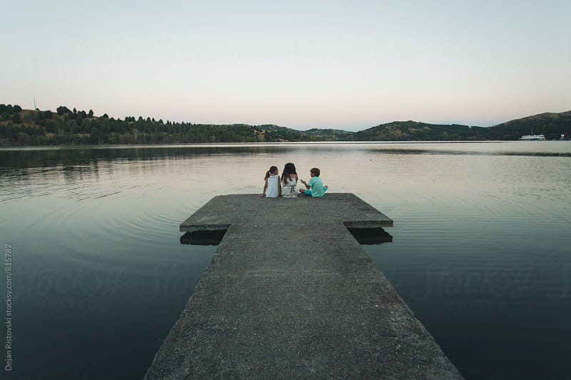 Friends sitting by lake by Dejan Ristovski for Stocksy United