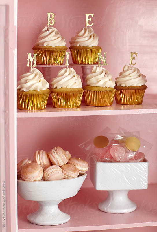 Be Mine gold letters on cupcakes in pink cabinet with macaroons and candy by Sherry Heck for Stocksy United