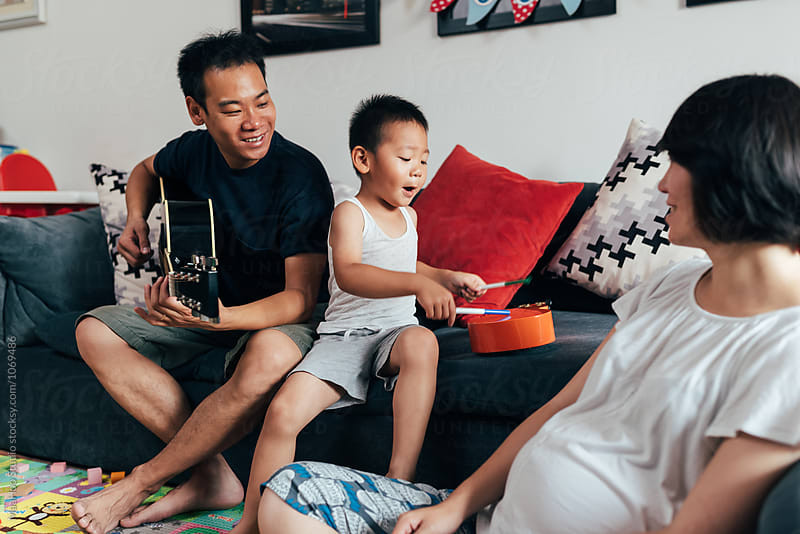 Father,pregnant mother and son playing instruments at home by Maa Hoo for Stocksy United