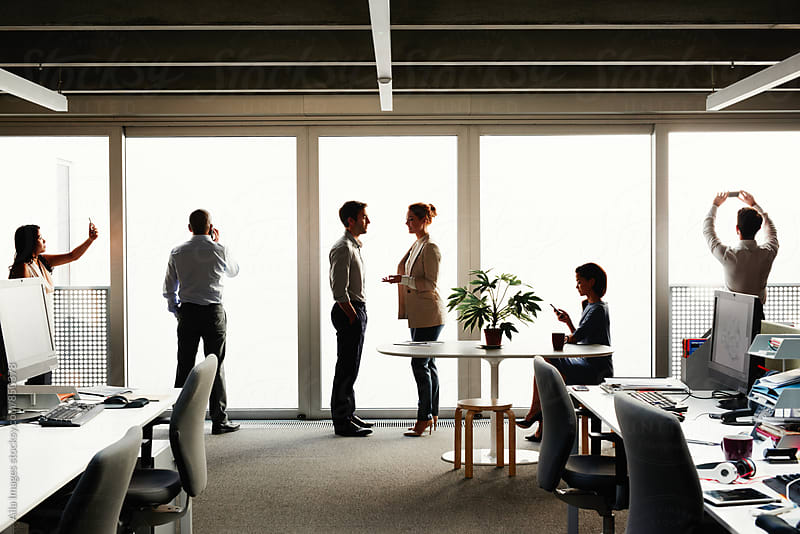 Profile silhouette of business team close to windows mulittasking by Aila Images for Stocksy United