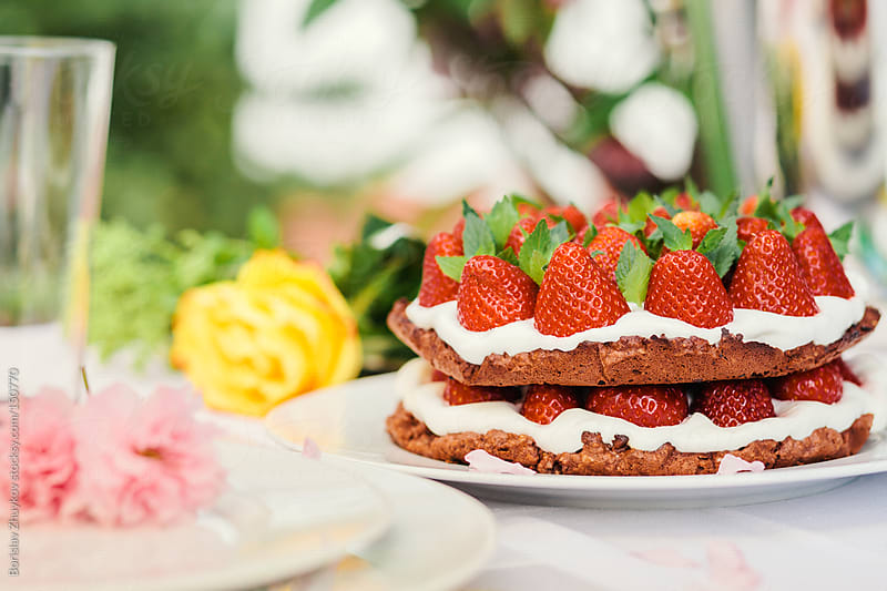 Homemade strawberry cake and decorated table with spring flowers by Borislav Zhuykov for Stocksy United