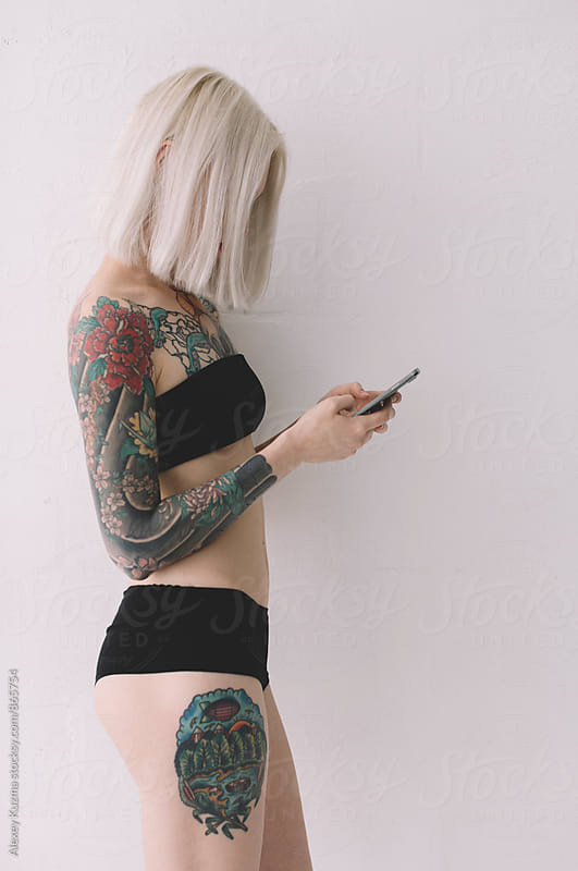 young blond woman  with tattoos on the phone by Alexey Kuzma for Stocksy United