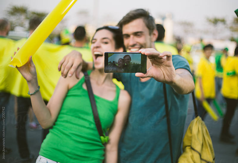 Two football fans taking a selfie after the game in Brazil by Jovo Jovanovic for Stocksy United