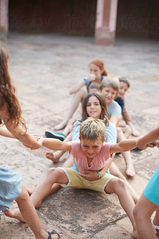 Group of children playing a game of energy and action by Miquel Llonch for Stocksy United